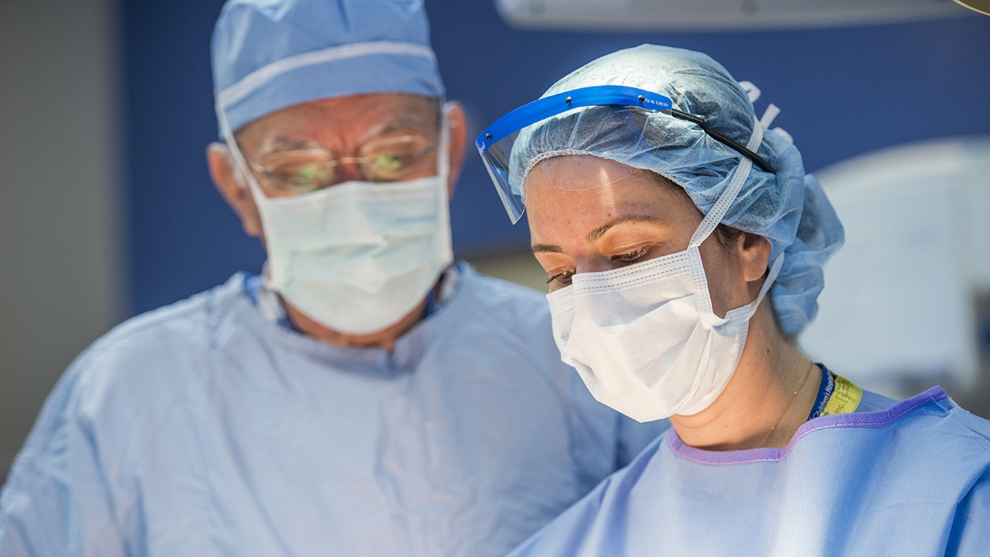 Alberto Peña, M.D. and Andrea Bischoff, M.D. are preforming colorectal surgery. Both surgeons are wearing masks and blue scrubs.