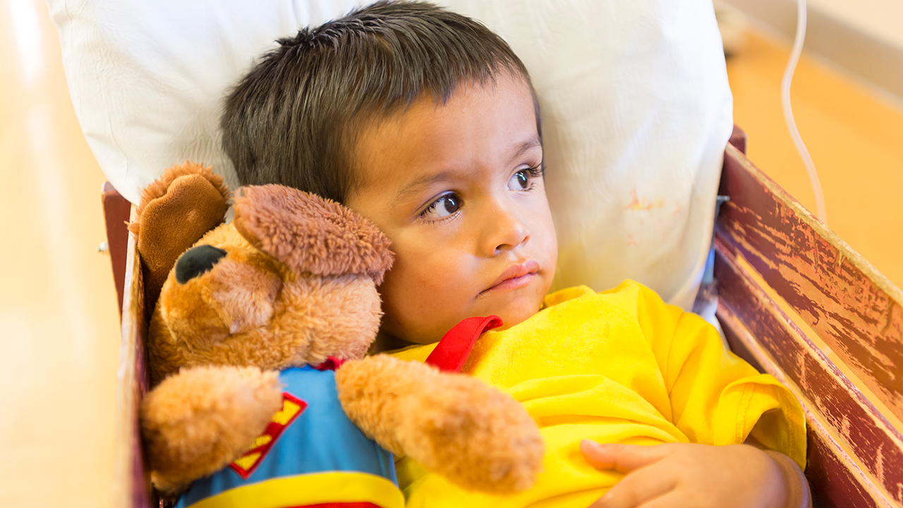 A young boy sits in a red wagon hugging a stuffed animal