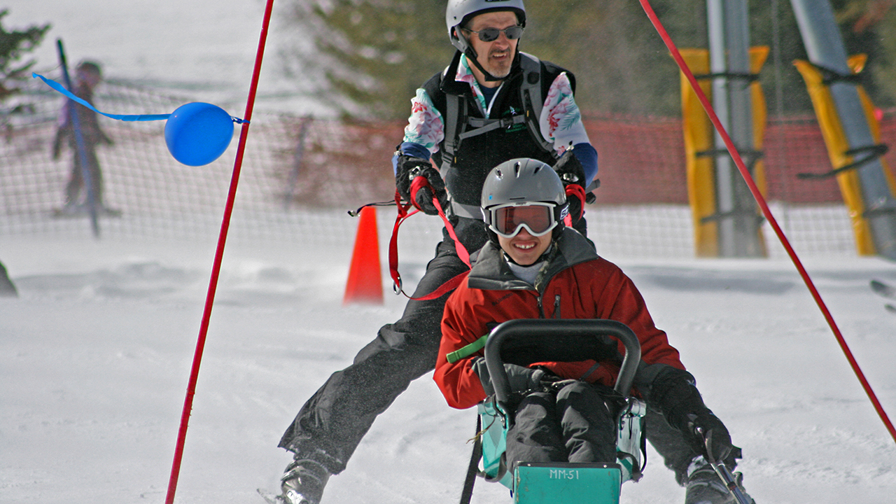 A kid in a red jacket, gray helmet and goggles rides in a green ski sled while a man in a black ski suit, gray helmet and sunglasses holds on with red straps.