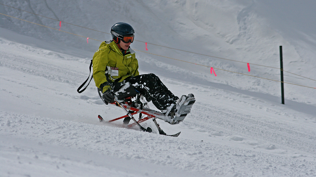 A kid going down a mountain on a ski sled
