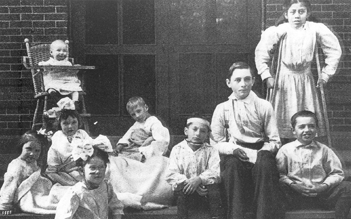 Old photo of child patients from 1910 including a baby in a wood high chair and a school age girl on crutches.