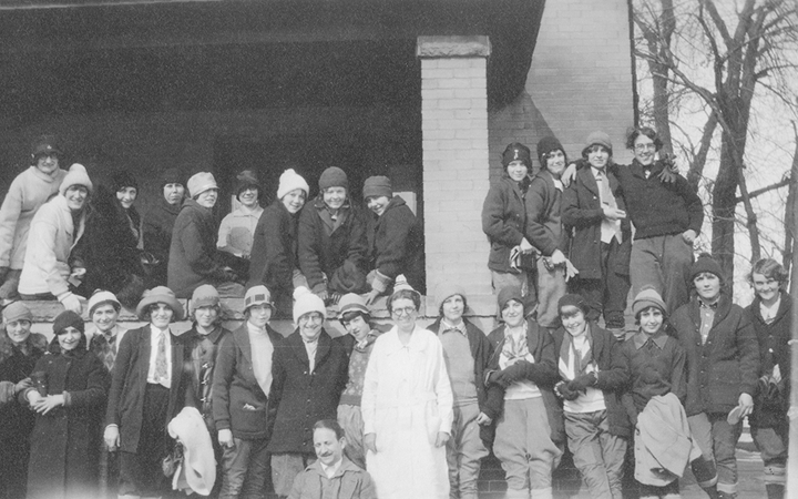 An old photo of about 30 kids gather on the porch - some sitting on the porch wall, others standing in front of it - with a woman in a white gown