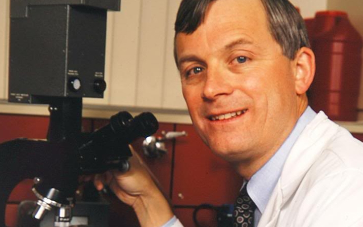 Dr. James Todd, wearing a white lab coat and tie, holds onto a microscope while he looks up and smiles.