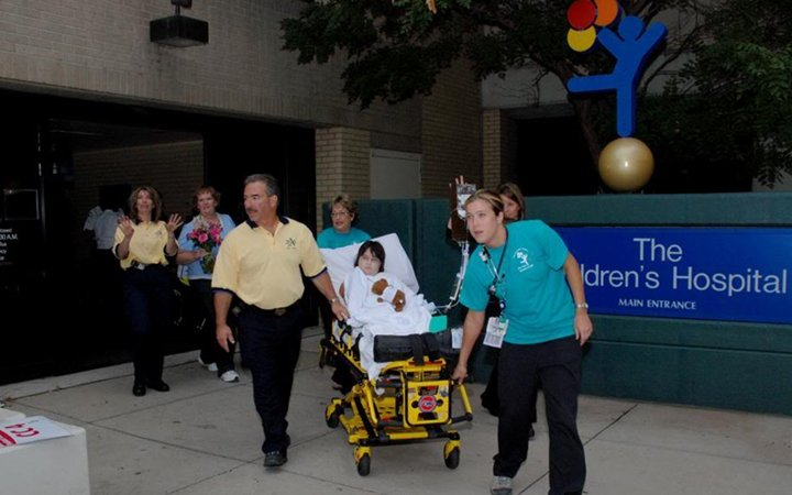 A child in a stretcher is wheeled out of the old Children's Hospital building