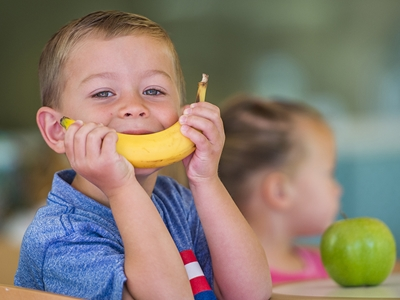 Young child eating a banana