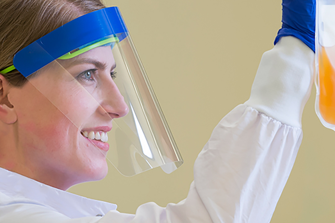 Woman in a laboratory wearing a face shield.