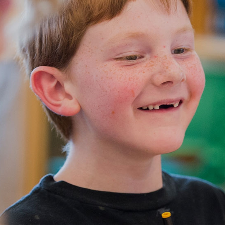 A close-up of a kid with freckles and red hair smiling with his two front teeth missing.
