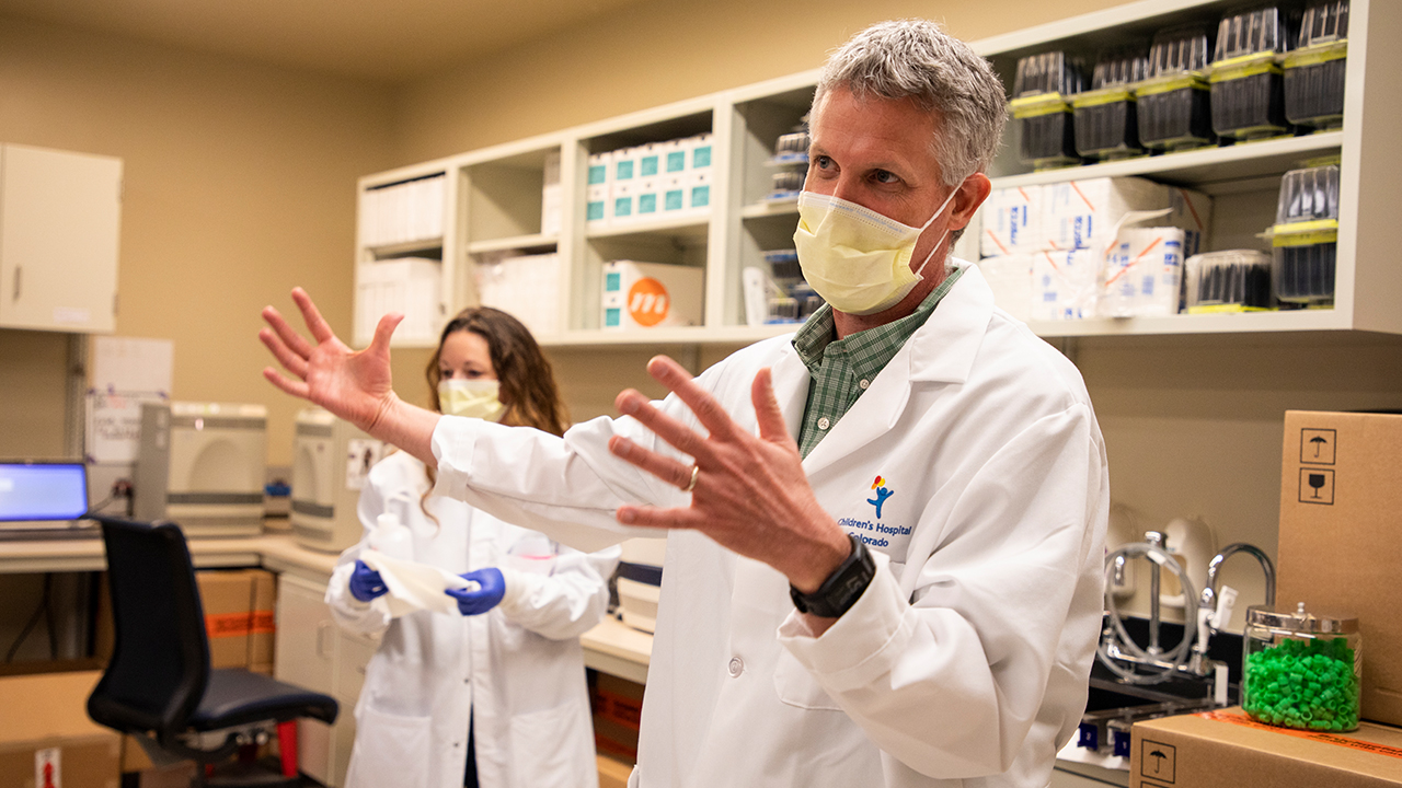 Dr. Sam Dominguez is pictured wearing a lab coat and face mask as he gestures in explanation.
