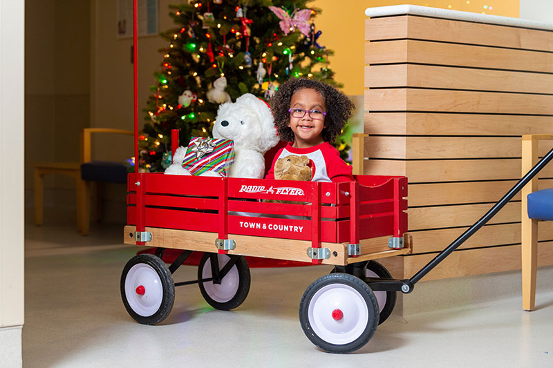 Nyssa in a red wagon. Holiday-themed