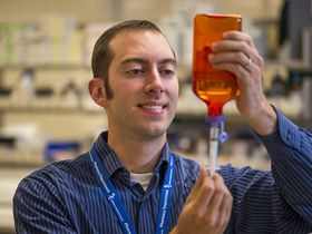 Researcher using syringe