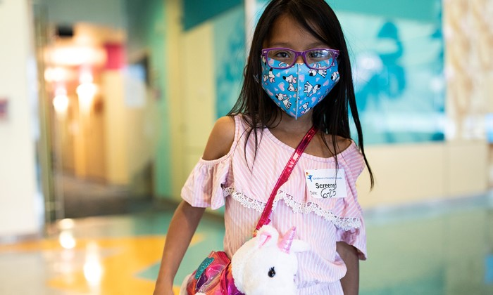 Young girl in glasses wearing a face covering and a purse shaped like a unicorn.