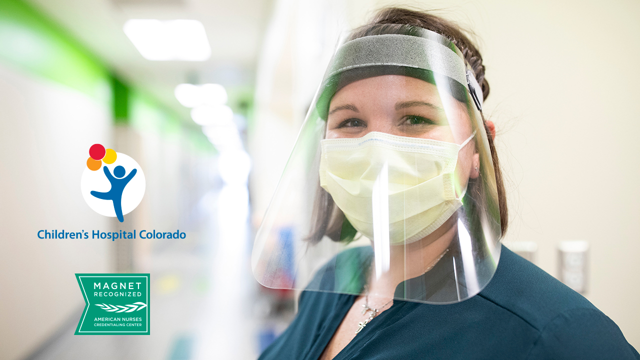 A nurse wearing a face mask and face shield smiles at the camera. A Magnet Recognition Logo is also on the image.
