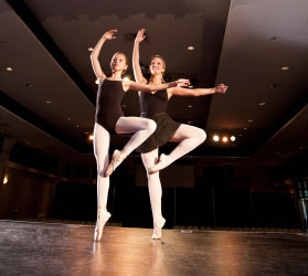 Two ballerinas in black leotards and white tights stand on one toe with the other foot held up by the knee, one arm up and one arm to the side.