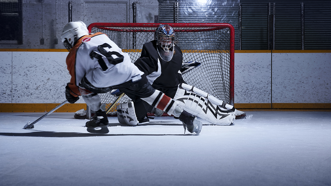 A hockey player approaches a goalie.