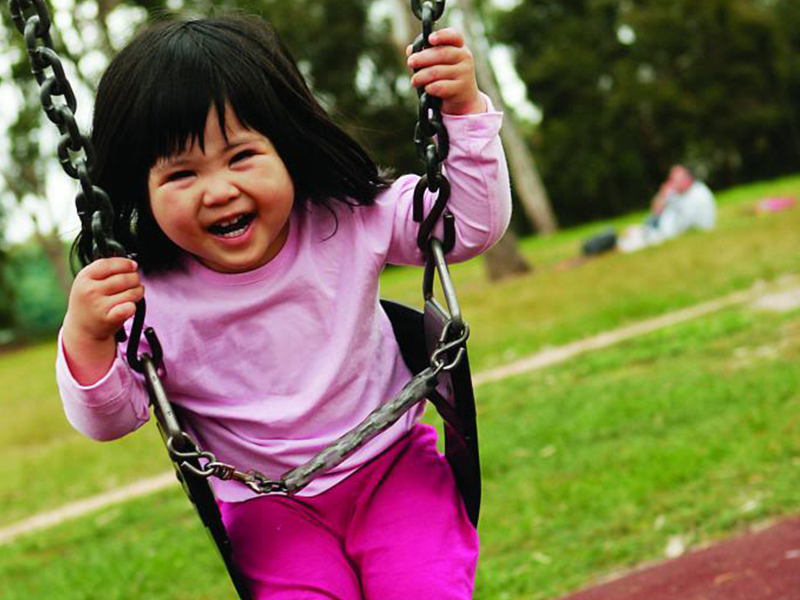 A young girl wearing a pink shirt safely swings outdoors in a park.