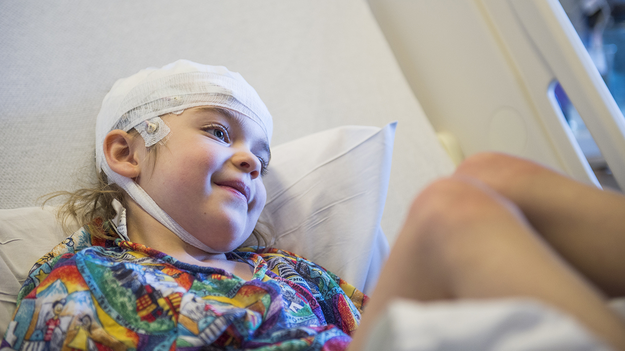 A kid lying in a hospital bed with bandages wrapped around her head