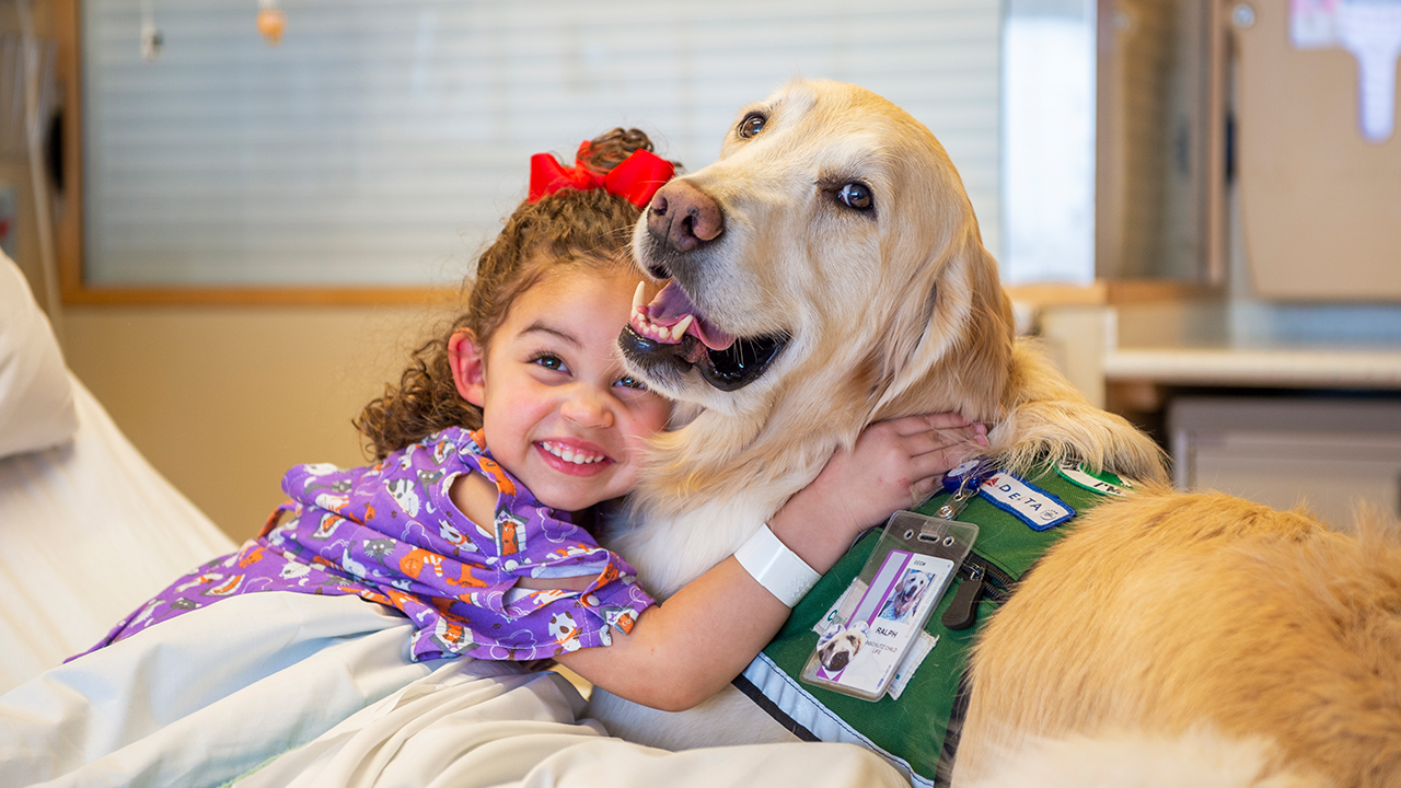 A child hugs a therapy dog