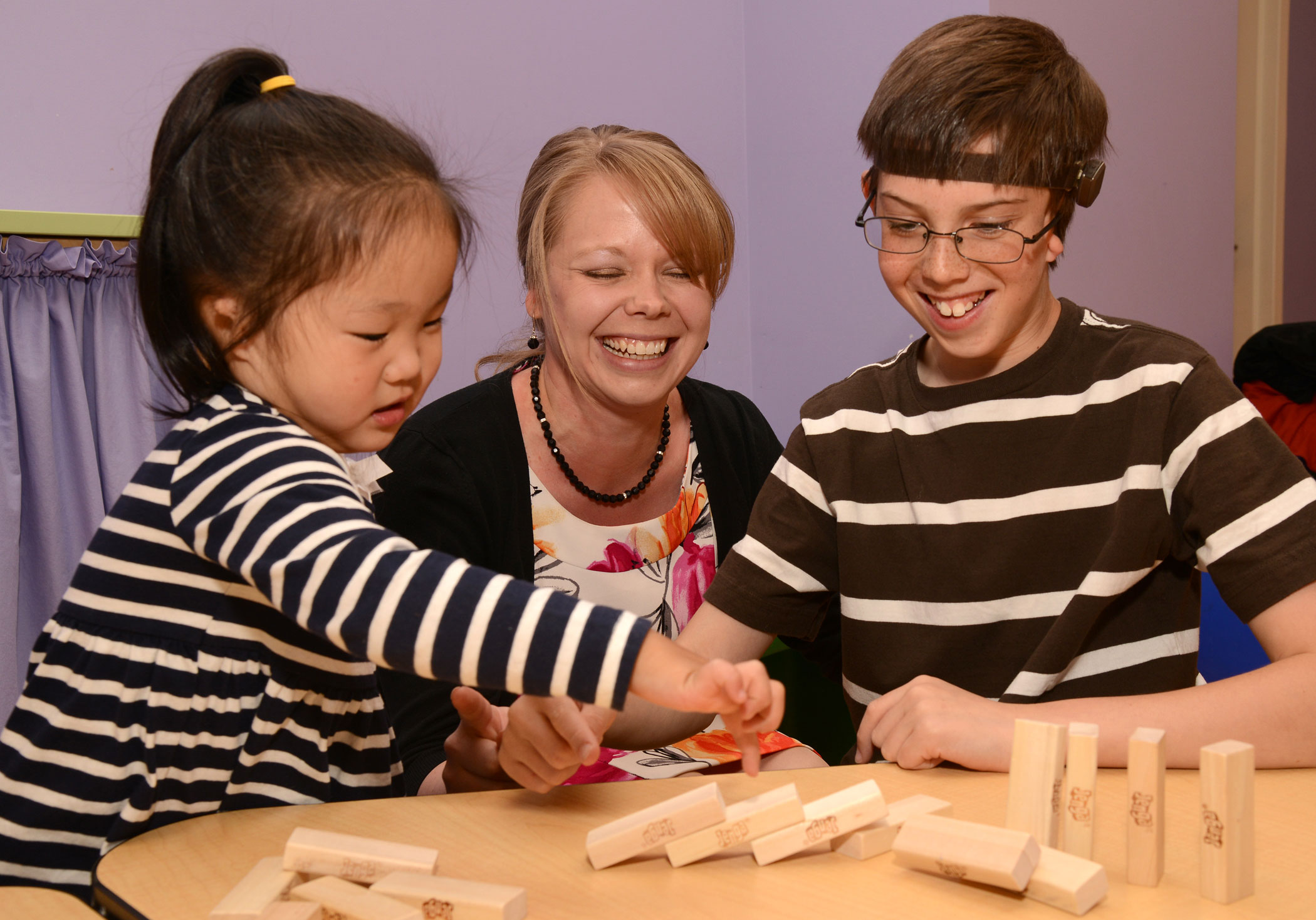 Audiologist Dr. Hedman sits in the middle of two patients playing Jenga. The girl on the left as her black hair in a ponytail and is wearing a black and white striped shirt. The boy on the right has glasses and is wearing a brown shirt with white stripes.