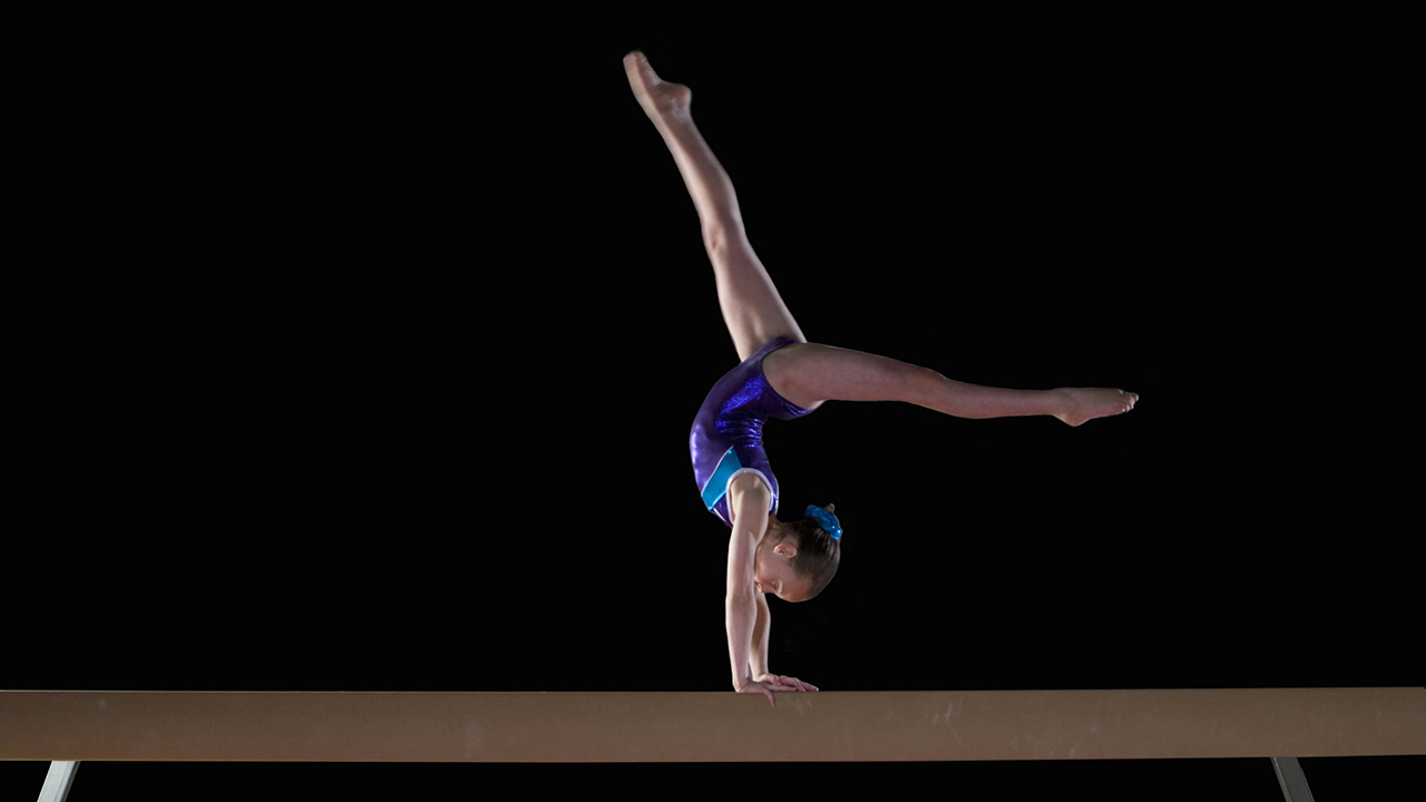 A gymnast performs on the balance beam