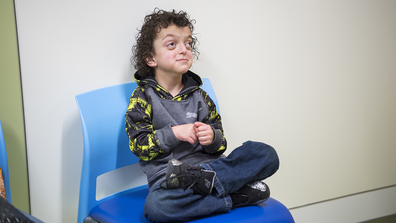 A craniofacial patient sits in a blue chair