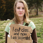 "A girl with long hair and wearing a short sleeve light green t-shirt over a long sleeve dark brown t-shirt holds a cardboard sign that says ""I cut class and now I am suspended""."