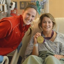 Missy Franklin, Olympic gold medalist, poses with a patient wearing her gold medal.