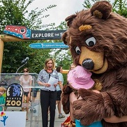 Children's Hospital Colorado's new mascot, Elbert the Bear, hugs a girl at the Denver Zoo.