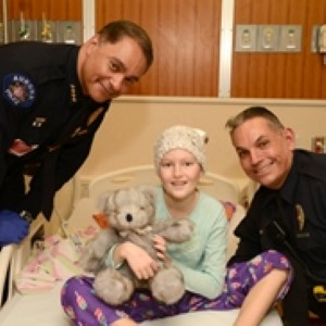 Aurora Police Chief Nick Metz (left) and Officer Jim Seneca deliver toys to patients in the Center for Cancer and Blood Disorders