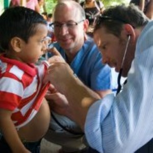 Dr. Edwin Asturias and Dr. James Gaensbauer, both pediatricians at Children's Colorado, examine children in a Guatemalan village.