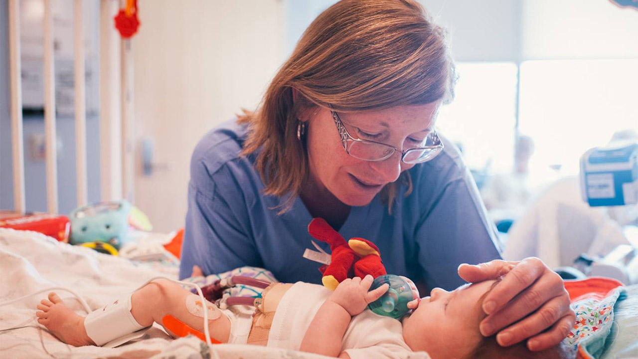 A provider cares for a baby at the Heart Institute