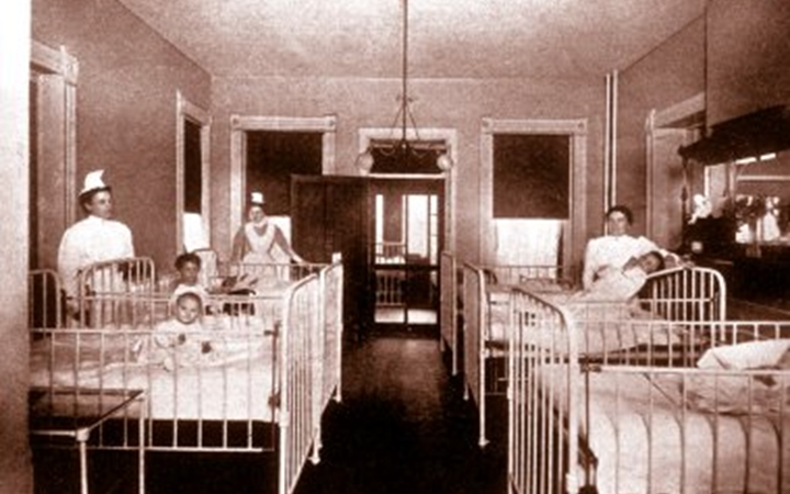 An old photo of the patient area in 1910 with two cribs on the left wall and three cribs on the right wall, three toddlers in the cribs and three nurses standing by