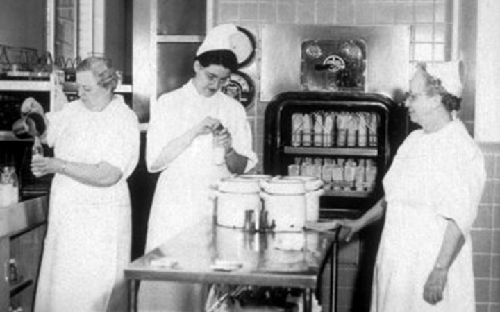 A black and photo of three nurses in white gowns and white hats standing around a cart holding three large canisters in the middle of the room. One is pouring liquid into a bottle, another is putting the cap on, and the third watches the other two.