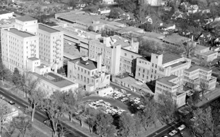 A black and white photo of an aerial view of a city block with a parking lot in the near corner and buildings filling the rest of the block. The building vary in height from three stories to eight stories and all have lots of windows.