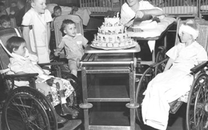 An old photo five kids, four in wheelchairs and one on crutches, sitting around a three-tier cake sitting on a cart