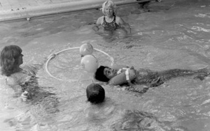 A black and white photo of two woman standing in a pool with balls and a hula hoop while two boys float in the water, one on his stomach with his head up and the other on his back wearing a life vest.