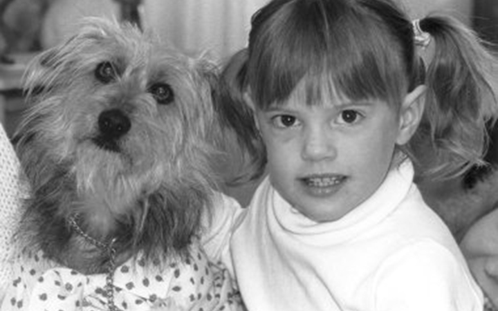 A black and white photo of a young girl with pigtails petting a small, shaggy dog