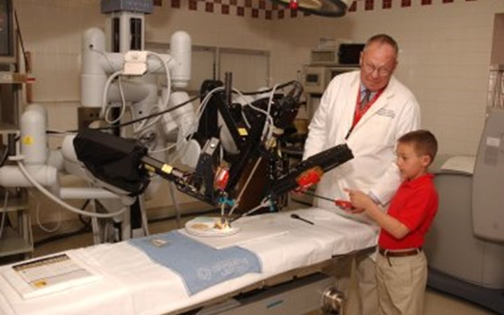 A school age boy wearing a red polo and khaki pants looks at the DaVinci Robot machine hovering over an operating table while a doctor in a white lab coat explains how it works.