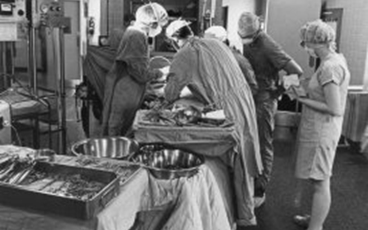 A black and white photo of an operating room with four surgeons working on a patient while a nurse looks on.
