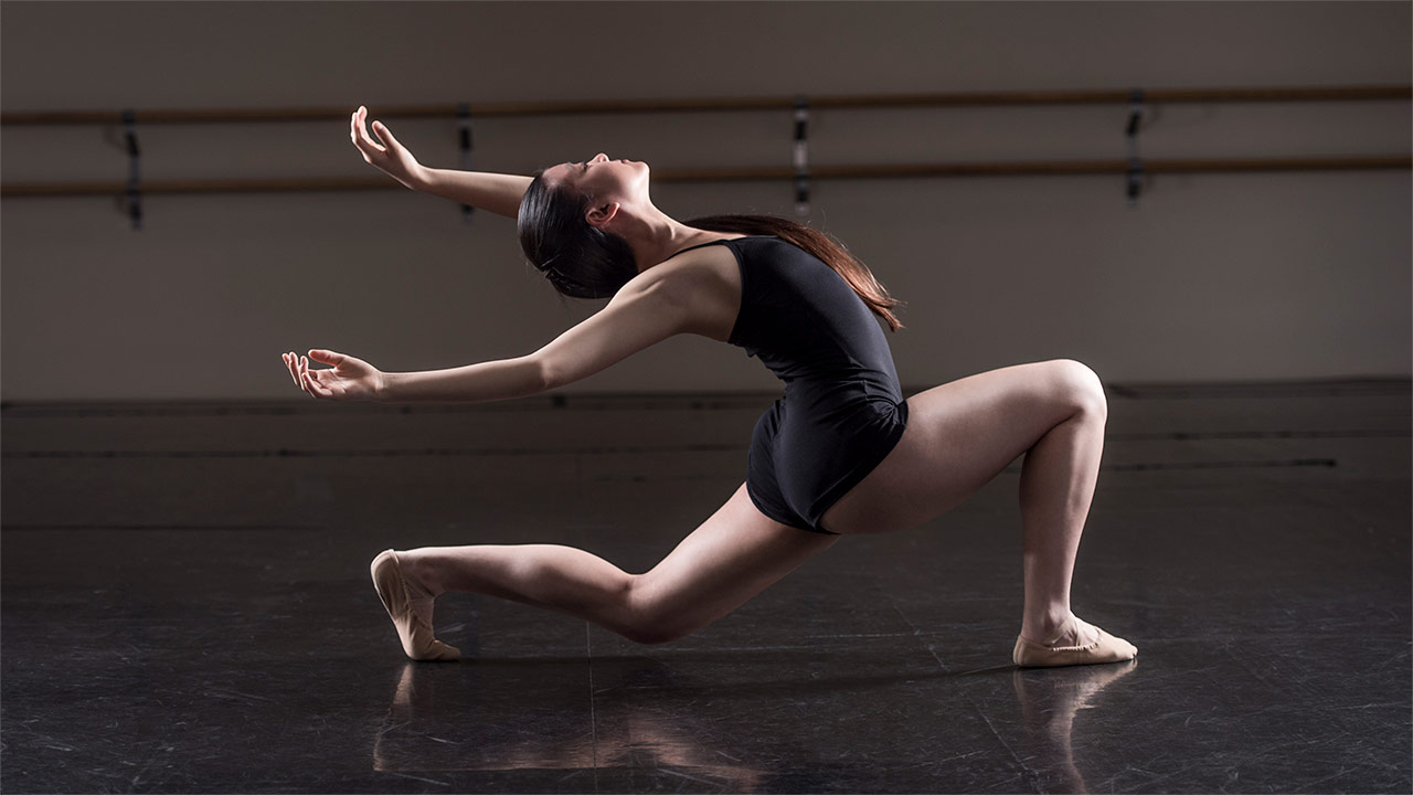 A teenage ballerina in a black leotard bends back low to the ground in a dance studio.