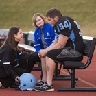 A football player sits on a bench with a coach and athletic trainer.