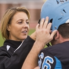 Athletic trainer helps football player adjust helmet.