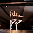 Two ballerinas dance on pointe in a theater.