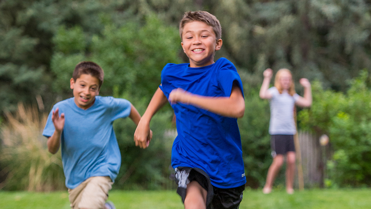 A boy in a bright blue shirt and black shorts races ahead of a boy in a light blue shirt and khaki shorts in a park full of green grass and trees.