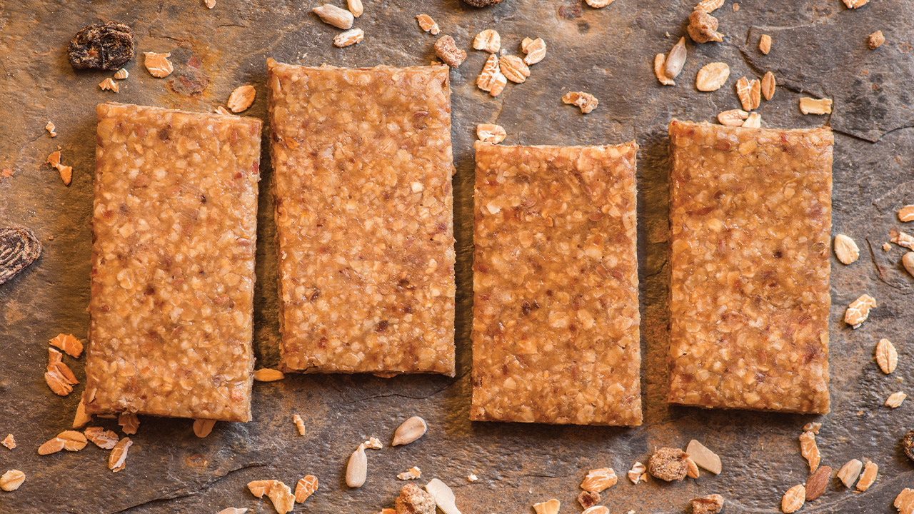 Four homemade energy bars for athletes that are a light brown color and made with oats and raisins.
