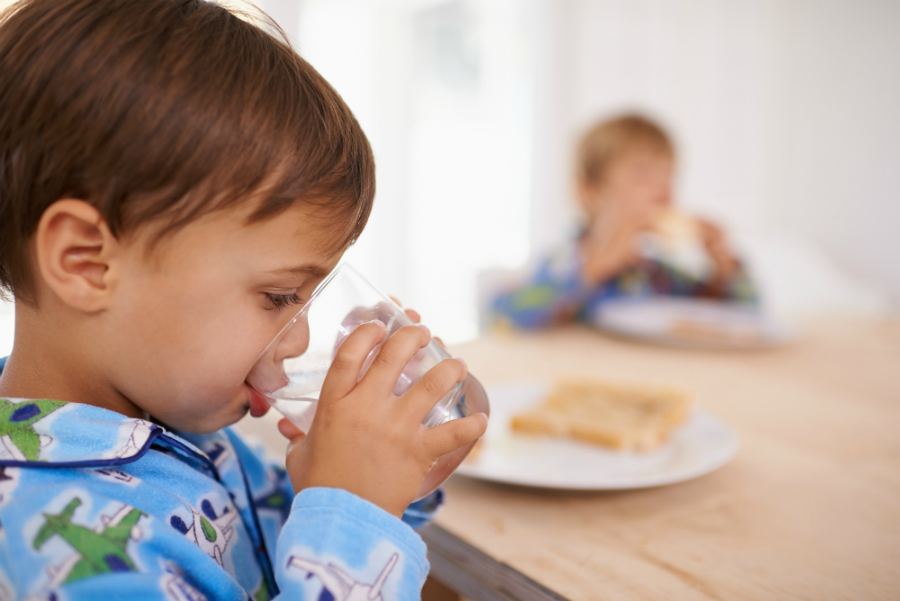 A young child with short brown hair is drinking a glass of water at the breakfast table as a healthy alternative to sugar-sweetened beverages like juice.
