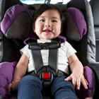 A baby sits in a purple car seat rear-facing inside of a car with gray interior. She has dark hair and is wearing a white shirt and blue pants. She's smiling.