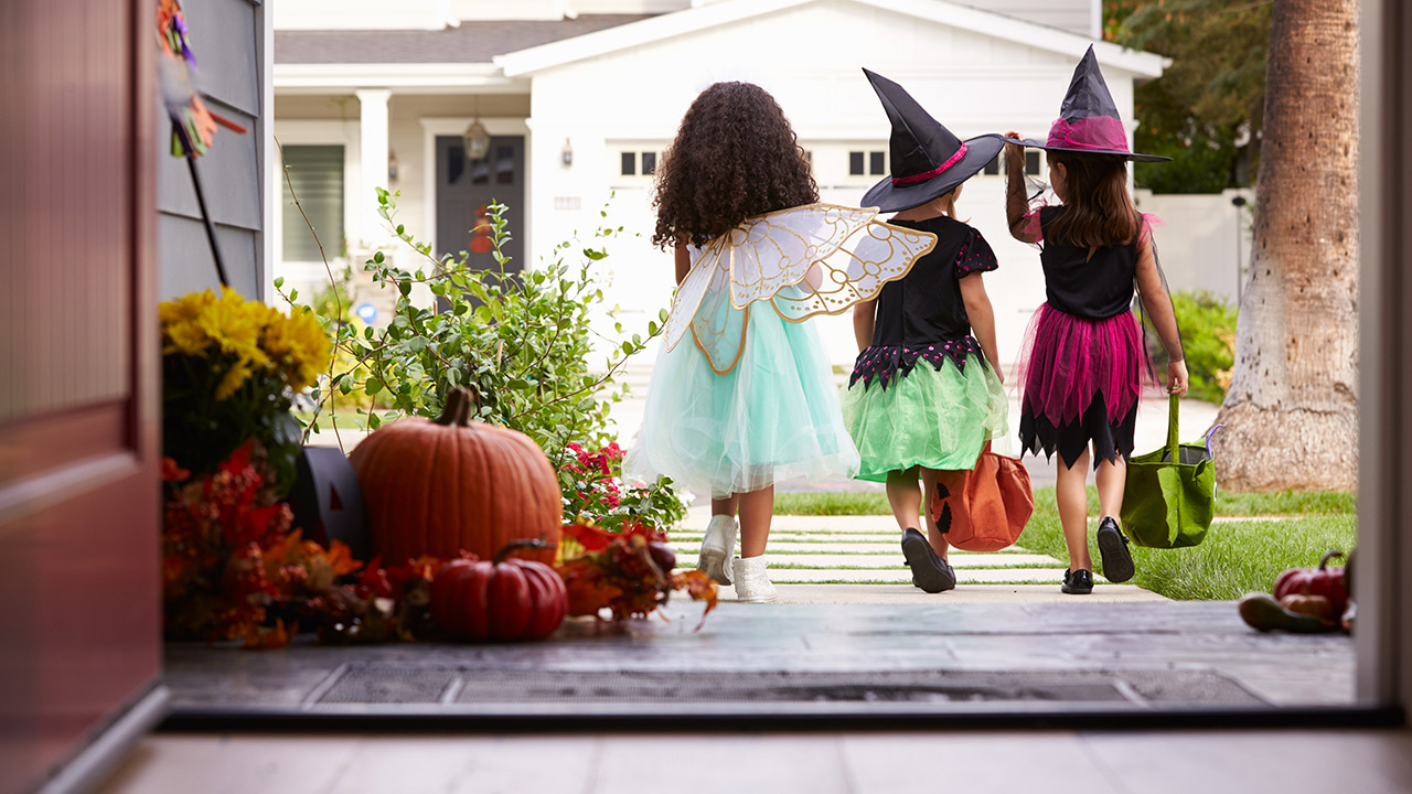 Three kids go trick-or-treating as a fairy with light blue princess dress and gold wings, a witch with black shirt, green skirt and black witch hat, and a witch in a black shirt, pink skirt and black witch hat.