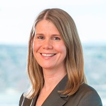 Headshot photograph of Jena Hausmann, president and CEO of Children's Hospital Colorado. She has shoulder length light brown hair and is wearing a gray suit jacket.