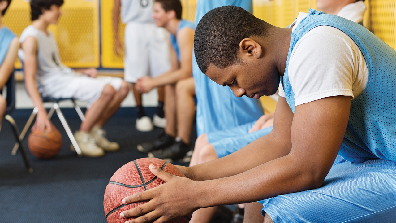 A basketball player sits on a bench in the locker room holding a basketball and looking down while his teammates look happy.