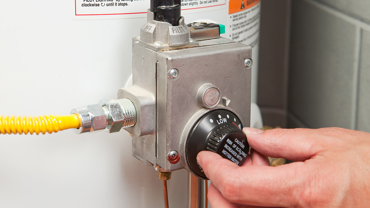 A closeup of a person's hand setting a black dial to Low on a white water heater.